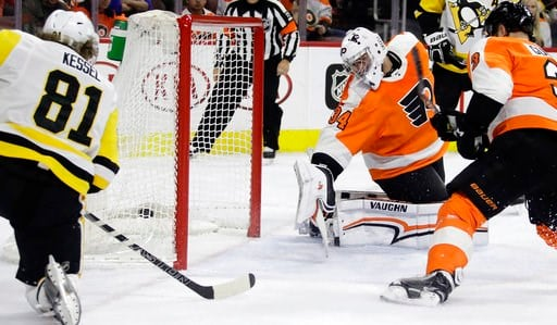 (AP Photo/Matt Slocum). Pittsburgh Penguins' Phil Kessel, left, scores a goal past Philadelphia Flyers' Petr Mrazek, center, and Radko Gudas during the first period of an NHL hockey game, Wednesday, March 7, 2018, in Philadelphia.