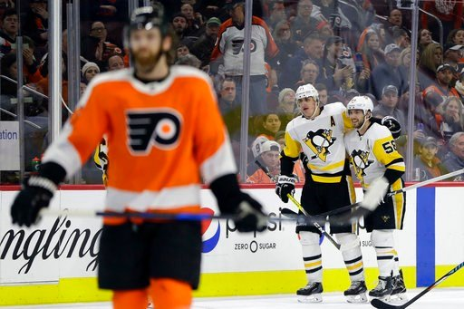 (AP Photo/Matt Slocum). Pittsburgh Penguins' Evgeni Malkin, center, and Kris Letang celebrate past Philadelphia Flyers' Sean Couturier, left, after a goal by Malkin during the third period of an NHL hockey game, Wednesday, March 7, 2018, in Philadelphi...