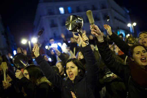 (AP Photo/Francisco Seco). Women bang pots and pans as shooting slogans during a protest marking the beginning of a 24-hour women strike at the Sol square in Madrid, early Thursday, March 8, 2018.