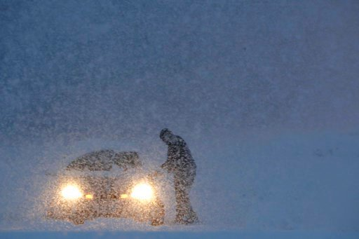 (AP Photo/Julio Cortez). A man gets into a vehicle on a snowbank on the exit to a business along Route 23 during a snowstorm, Wednesday, March 7, 2018, in Wayne, N.J.