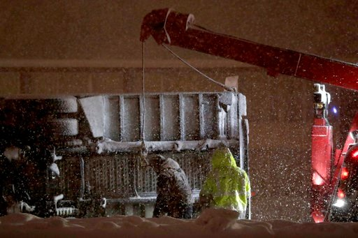 (AP Photo/Julio Cortez). Tow truck operators attach lines to a rolled over tractor trailer during a snowstorm, Wednesday, March 7, 2018, in Wayne, N.J.