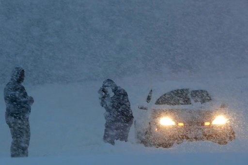 (AP Photo/Julio Cortez). People stand near a vehicle stuck on a snowbank along Route 23 during a snowstorm, Wednesday, March 7, 2018, in Wayne, N.J.