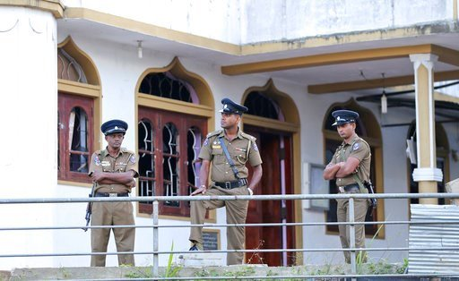 (AP Photo/Rukmal Gamage). Sri Lankan police officers stand outside a vandalized Mosque in Poojapitiya, in central Sri Lanka, Wednesday, March 7, 2018. Sri Lanka's president declared a state of emergency Tuesday amid fears that anti-Muslim attacks in se...