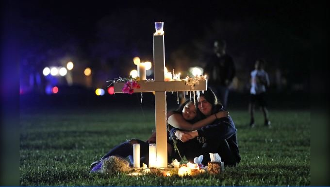 Two people comfort each other as they sit and mourn at one of seventeen crosses after a candlelight vigil for the victims of the Wednesday shooting at Marjory Stoneman Douglas High School, in Parkland, Fla., Thursday, Feb. 15, 2018. (AP Photo/Gerald Herb)
