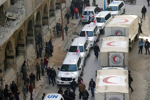 (Syrian Red Crescent via AP). This photo released by the Syrian Red Crescent shows civilians gathering near a convoy of vehicles of the Syrian Red Crescent in Douma, eastern Ghouta, a suburb of Damascus, Syria, Monday, March. 5, 2018. Desperate for foo...