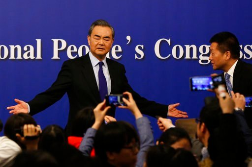 "(AP Photo/Andy Wong). China's Foreign Minister Wang Yi, left, gestures to journalists during a press conference on the sidelines of the National People's Congress at the media center in Beijing, Thursday, March 8, 2018. China says its proposal for a ""d..."