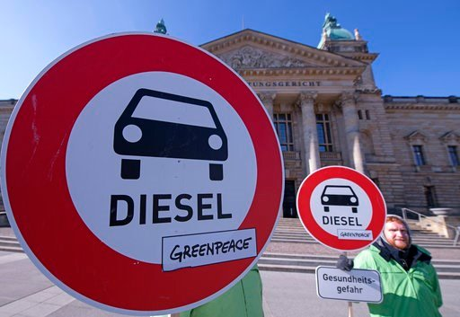 (AP Photo/Jens Meyer,file). FILE - In this Feb. 27, 2018 file photo Environment activists stand in front of the Federal Administrative Court prior to a trial in Leipzig, Germany. The German court ruled  that cities can impose driving bans on diesel car...
