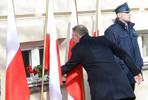 (AP Photo/Alik Keplicz). Polish President Andrzej Duda lays flowers during ceremonies marking the 50th anniversary of student protests that were exploited by the communists to purge Jews from Poland, at the Warsaw University in Warsaw, Poland, Thursday...