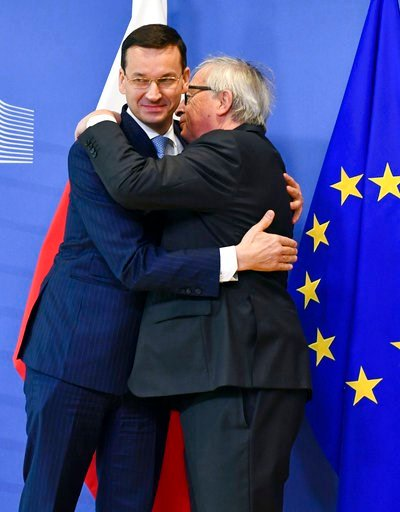 (AP Photo/Geert Vanden Wijngaert). European Commission President Jean-Claude Juncker, right, greets Polish Prime Minister Mateusz Morawiecki prior to a meeting at EU headquarters in Brussels on Thursday, March 8, 2018.