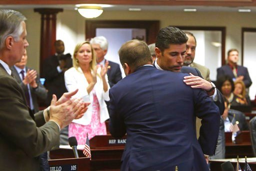 (Scott Keeler/Tampa Bay Times via AP). Rep. Jose Oliva, R- Miami Lakes, is hugged and congratulated by House members as the gun and school safety bill passed the Florida House 67-50 in Tallahassee, Fla., Wednesday, March 7, 2018. Oliva shepherd the bil...
