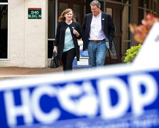 (Brett Coomer/Houston Chronicle via AP). In this March 6, 2018, photo, Lizzie Pannill Fletcher and her husband, Scott Fletcher, walk out of the polling place at St. Anne's Catholic Church after voting in the primary election in Houston. Democrats are s...