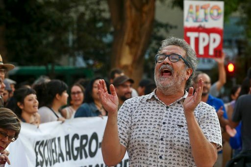(AP Photo/Esteban Felix). A man shout slogans during a demonstration against the signing of the Trans-Pacific Partnership, TPP, outside La Moneda presidential palace, in Santiago, Chile, Wednesday, March 7, 2018. Protesters voiced their opposition to t...