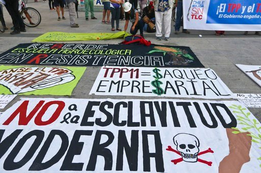(AP Photo/Esteban Felix). A woman places banners on the sidewalk, against the signing of the Trans-Pacific Partnership, TPP, outside La Moneda presidential palace, in Santiago, Chile, Wednesday, March 7, 2018. Protesters voiced their opposition to the ...