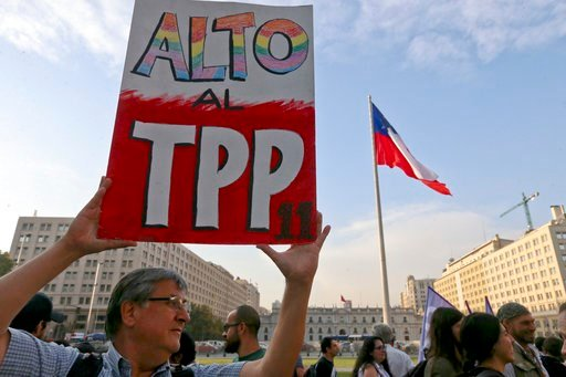 (AP Photo/Esteban Felix). A man holds a sign against the signing of the Trans-Pacific Partnership, TPP, during a demonstration outside La Moneda presidential palace, in Santiago, Chile, Wednesday, March 7, 2018. Protesters voiced their opposition to th...