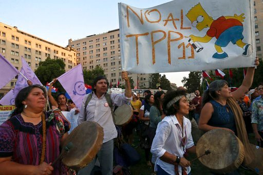(AP Photo/Esteban Felix). People take part in a demonstration against the Trans-Pacific Partnership, TPP, outside La Moneda presidential palace, in Santiago, Chile, Wednesday, March 7, 2018. Protesters voiced their opposition to the signing of the 11-c...