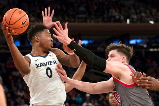 (AP Photo/Mary Altaffer). Xavier forward Tyrique Jones (0) looks to pass the ball around St. John's forward Amar Alibegovic (10) during the first half of an NCAA college basketball game in the quarterfinals of the Big East conference tournament, Thursd...