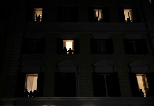 (AP Photo/Alessandra Tarantino). People are silhouetted as they peer out windows to look at a women's demonstration to mark the international Women's Day in Rome, Thursday, March 8, 2018.