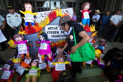 (AP Photo/Moises Castillo). An activist places a doll representing one of the 41 girls that died in a fire one year ago at the state-run Virgen de la Asuncion youth shelter, during a rally to mark International Women's Day in Guatemala City, Thursday, ...