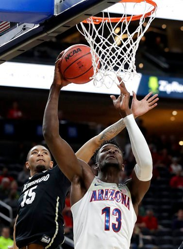 (AP Photo/Isaac Brekken). Colorado's Dominique Collier, left, covers a shot from Arizona's Deandre Ayton during the first half of an NCAA college basketball game in the quarterfinals of the Pac-12 men's tournament Thursday, March 8, 2018, in Las Vegas.