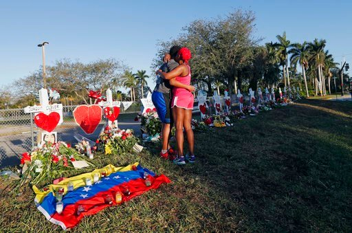 (AP Photo/Gerald Herbert, File). FILE - This Feb. 19, 2018 file photo shows Denyse Christian, hugging her son Adin Christian, 16, a student at the school, at a makeshift memorial outside the Marjory Stoneman Douglas High School, where 17 students and f...