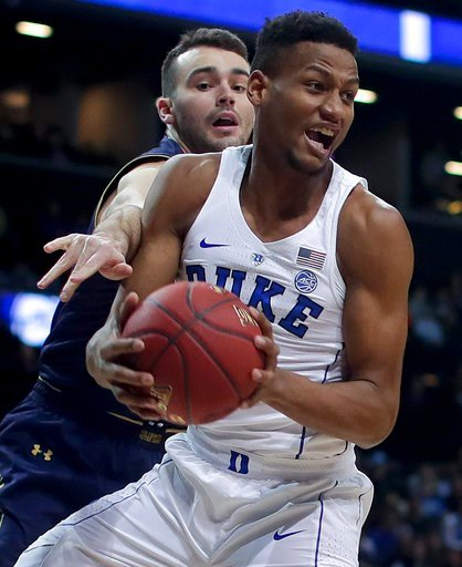 (AP Photo/Julie Jacobson). Duke forward Javin DeLaurier (12) pulls down a rebound against Notre Dame forward John Mooney (33) during the first half of an NCAA college basketball game in the Atlantic Coast Conference men's tournament Thursday, March 8, ...