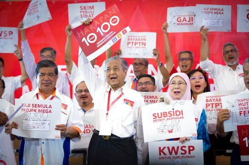 (AP Photo/Vincent Thian). Malaysia's former Prime Minister Mahathir Mohamad, center, and Wan Azizah, wife of former Deputy Prime Minister Anwar Ibrahim, center left, shout slogans with other opposition leaders during a political opposition alliance eve...