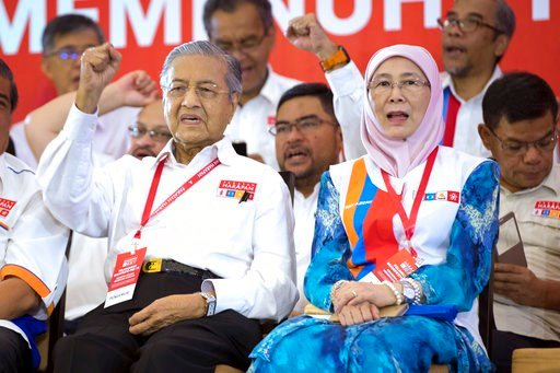 (AP Photo/Vincent Thian). Malaysia's former Prime Minister Mahathir Mohamad, left, and Wan Azizah, wife of former Deputy Prime Minister Anwar Ibrahim, shout slogans during a political opposition alliance event in Shah Alam, Malaysia on Thursday, March ...