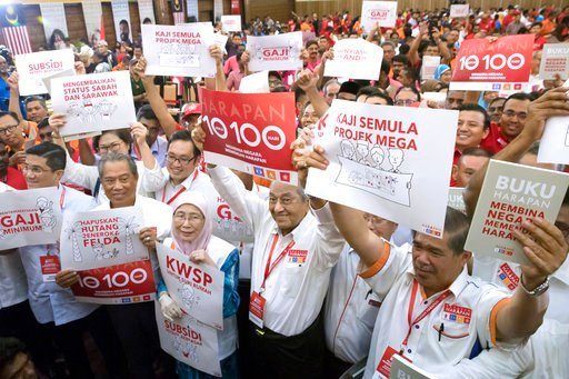 """(AP Photo/Vincent Thian). Malaysia's former Prime Minister Mahathir Mohamad, center, displays the opposition manifesto placard during a political opposition alliance event in Shah Alam, Malaysia on Thursday, March 8, 2018. Opposition coalition """"Pakatan..."""