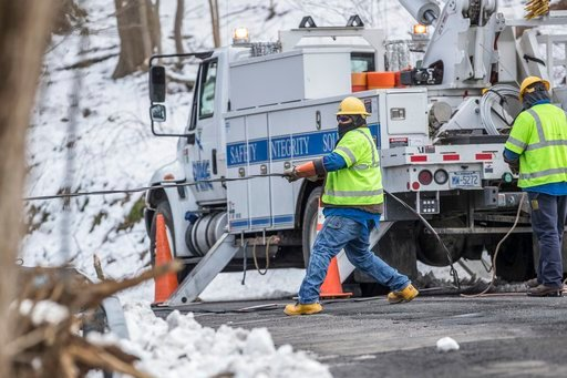 (Michael Bryant/The Philadelphia Inquirer via AP). Crew members from PIKE electric company from Maryland pull a downed power line on New Road in Aston, Pa., in order to reconnect it on Thursday, March 8, 2018. Pennsylvania utility companies say more th...