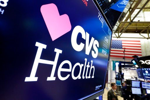(AP Photo/Richard Drew, File). FILE- In this Dec. 4, 2017, file photo, the CVS Health logo appears above a trading post on the floor of the New York Stock Exchange. Insurers are dropping billions of dollars on acquisitions and expansions as they get mo...