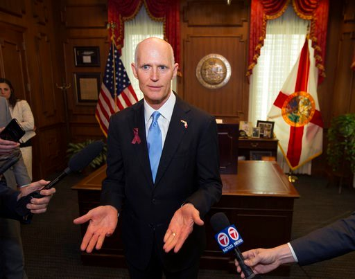 (AP Photo/Mark Wallheiser). Florida Gov. Rick Scott talks to the media in his office after signing the Marjory Stoneman Douglas Public Safety Act at the Florida Capital in Tallahassee, Fla., Friday, March 9, 2018.