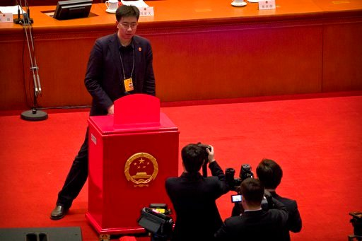 (AP Photo/Mark Schiefelbein). A staff member stands in front of a ballot box on the rostrum before a plenary session of China's National People's Congress (NPC) at the Great Hall of the People in Beijing, Sunday, March 11, 2018.
