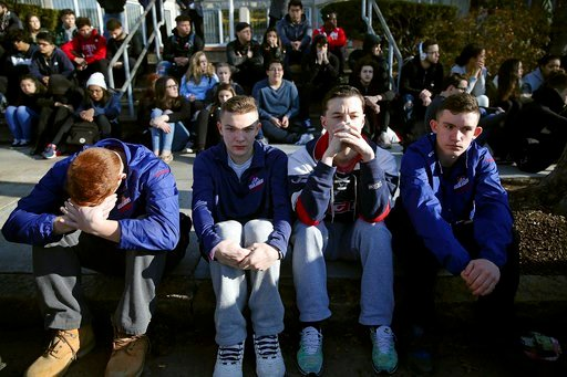 (Craig F. Walker/The Boston Globe via AP). In this Feb. 28, 2018 photo, Somerville High School students sit on the sidewalk on Highland Avenue during a student walkout at the school in Somerville, Mass. A large-scale, coordinated demonstration is plann...