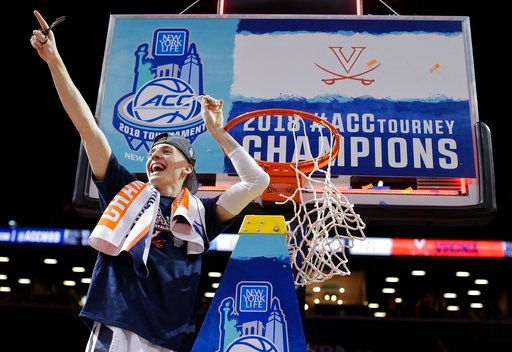 (AP Photo/Julie Jacobson). Virginia guard Kyle Guy celebrates after cutting a piece of the net after his team defeated North Carolina in the championship game of the NCAA Atlantic Coast Conference men's tournament Saturday, March 10, 2018, in New York.