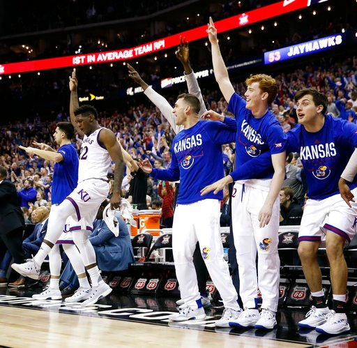 (AP Photo/Charlie Riedel). Kansas players celebrate during the second half of the NCAA college basketball championship game against West Virginia in the Big 12 men's tournament Saturday, March 10, 2018, in Kansas City, Mo. Kansas won 81-70.