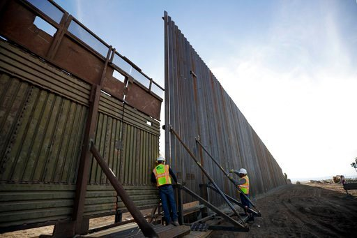 (AP Photo/Gregory Bull). In this March 5, 2018, photo, a worker looks between the first section of a newly-constructed structure along the border separating Mexicali, Mexico and Calexico, Calif. As Donald Trump prepares for his first visit to the U.S.-...