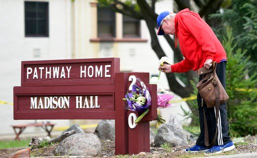 (AP Photo/Josh Edelson). Resident Tom Parkinson places flowers on a sign at the Veterans Home of California, the morning after a hostage situation in Yountville, Calif., on Saturday, March 10, 2018.