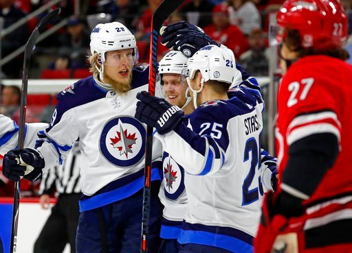 (AP Photo/Karl B DeBlaker). Winnipeg Jets' Patrik Laine (29) celebrates his goal with teammates Nikolaj Ehlers (27) and Paul Stastny (25) during the first period of an NHL hockey game against the Carolina Hurricanes, Sunday, March 4, 2018, in Raleigh, ...
