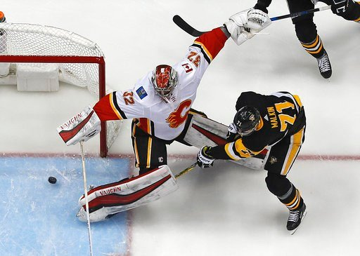 (AP Photo/Gene J. Puskar). Pittsburgh Penguins' Evgeni Malkin (71) gathers the puck and prepares to put it behind Calgary Flames goaltender Jon Gillies (32) for a goal in the first period of an NHL hockey game in Pittsburgh, Monday, March 5, 2018.
