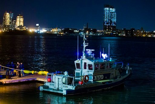 (AP Photo/Andres Kudacki). Yellow buoys that a New York police officer said are suspending a helicopter that crashed on the East River float next to a NYPD police boat at a pier in New York on Sunday, March 11, 2018.