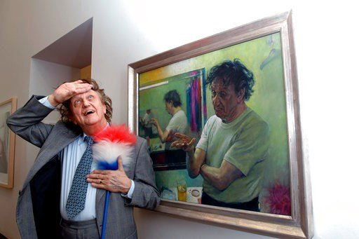 (Fiona Hanson/PA via AP, File). FILE - In this Aug. 17, 2005 file photo, comedian Ken Dodd poses with a new oil on canvas portrait of himself entitled 'Ken Dodd. Entertainer' by Wiltshire artist David Cobley. British comedian Ken Dodd, whose seven-deca...