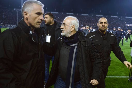(AP Photo). In this photo taken on Sunday, March 11, 2018, PAOK owner, businessman Ivan Savvidis, center, escorted by his bodyguards leaves the pitch during a Greek League soccer match between PAOK and AEK Athens in the northern Greek city of Thessalon...