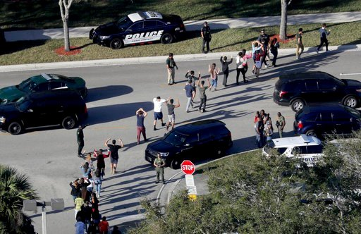 (Mike Stocker/South Florida Sun-Sentinel via AP, File). FILE - In this Feb. 14, 2018 file photo, students hold their hands in the air as they are evacuated by police from Marjory Stoneman Douglas High School in Parkland, Fla., after a shooter opened fi...