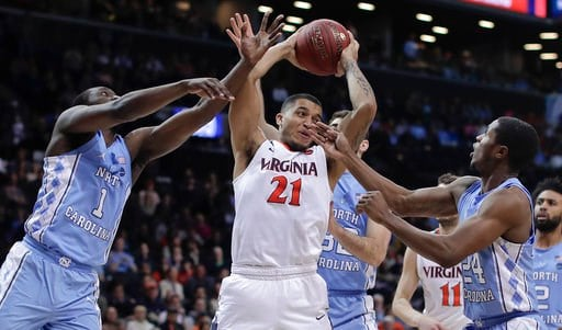 (AP Photo/Julie Jacobson). Virginia forward Isaiah Wilkins (21) pulls down a rebound between North Carolina forward Theo Pinson (1), guard Kenny Williams (24) and forward Luke Maye (32) during the second half of an NCAA college basketball game for the ...
