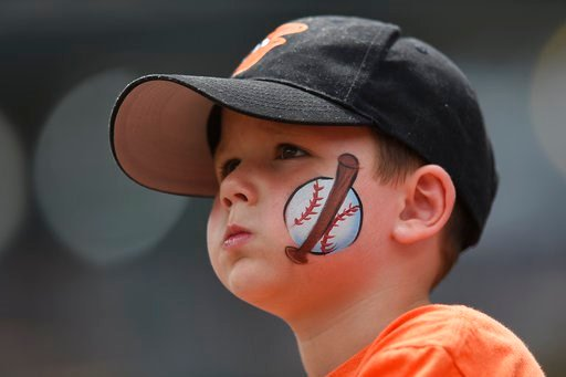 (AP Photo/Gail Burton, File). FILE - In this Aug. 6, 2017, file photo, a young baseball fan looks on before the Baltimore Orioles and Detroit Tigers baseball game, in Baltimore. The Orioles have launched a program that will enable kids to attend home g...