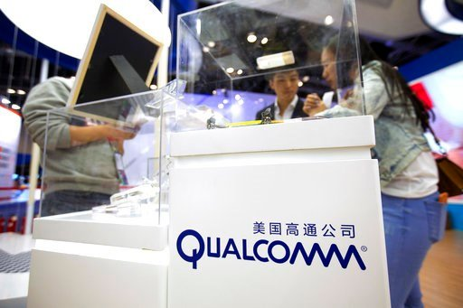 (AP Photo/Mark Schiefelbein, File). FILE - In this Thursday, April 27, 2017, file photo, visitors look at a display booth for Qualcomm at the Global Mobile Internet Conference (GMIC) in Beijing. On Monday, March 12, 2018, President Donald Trump blocked...
