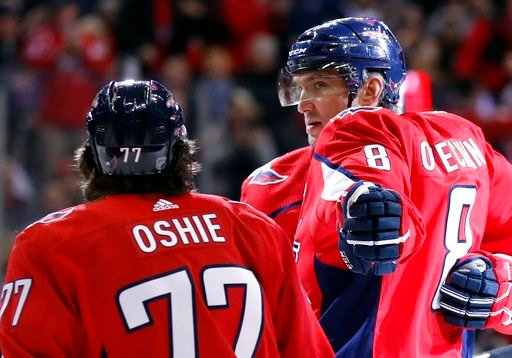 (AP Photo/Alex Brandon). Washington Capitals left wing Alex Ovechkin (8) reaches to celebrate with right wing T.J. Oshie (77) after scoring in the first period of an NHL hockey game against the Winnipeg Jets, Monday, March 12, 2018, in Washington.
