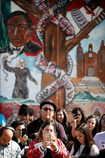 (AP Photo/Gregory Bull). People look on in front of a mural depicting heroes of the Mexican revolution during a rally against a scheduled upcoming visit to the area by President Donald Trump Monday, March 12, 2018, in San Diego. Trump is scheduled to v...