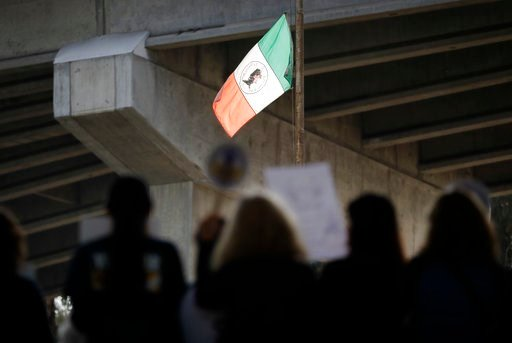 (AP Photo/Gregory Bull). People attend a rally against a scheduled upcoming visit to the area by President Donald Trump as a flag fashioned after the flag of Mexico flies over Chicano Park Monday, March 12, 2018, in San Diego. Trump is scheduled to vis...