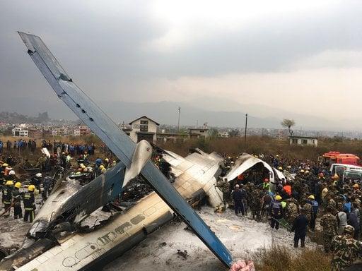 (AP Photo/Niranjan Shreshta). Nepalese rescuers stand near a passenger plane from Bangladesh that crashed at the airport in Kathmandu, Nepal, Monday, March 12, 2018.